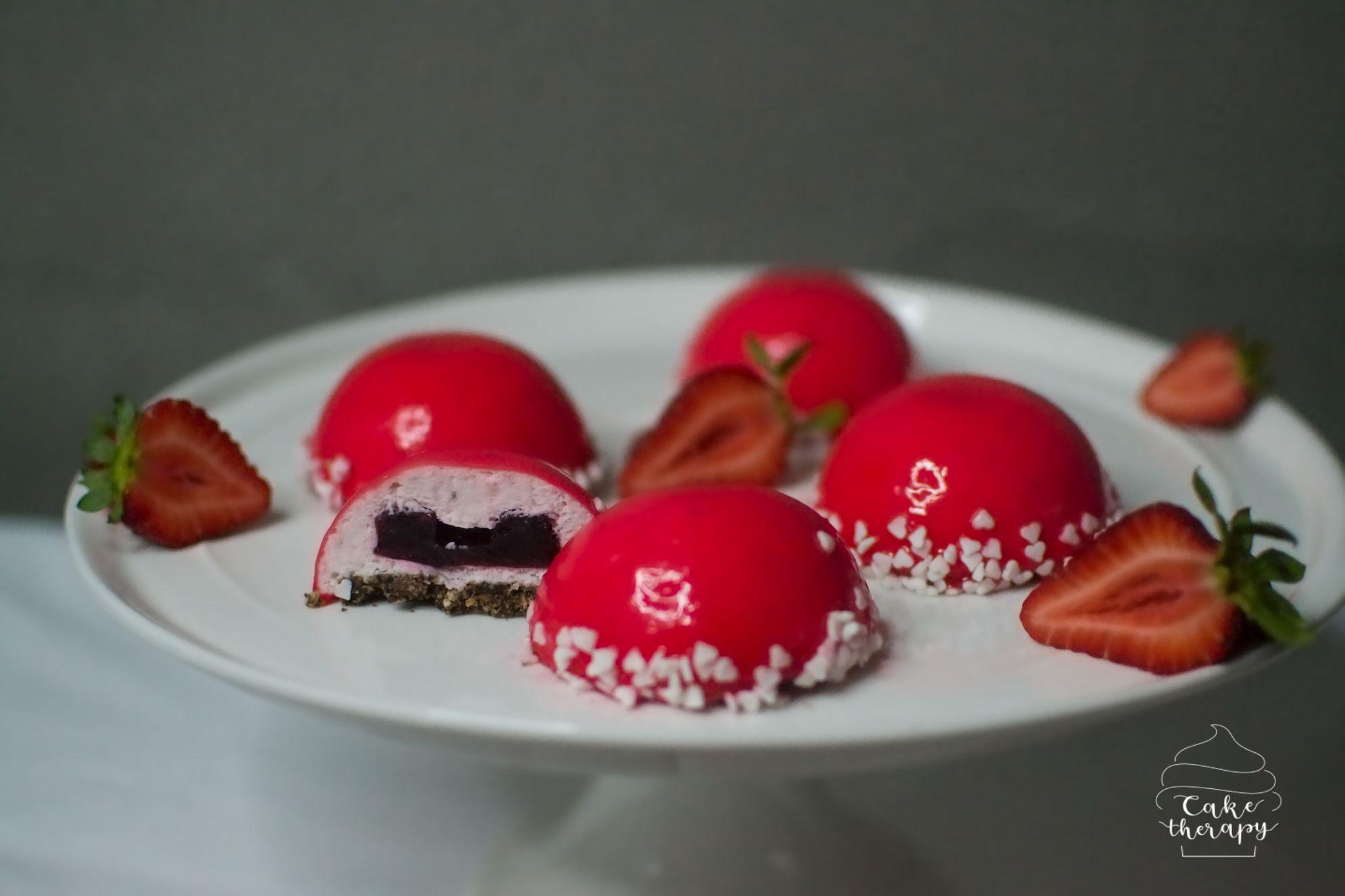 Świeże truskawki i śmietanka kremówka w postaci musu, żelka ze świeżych jeżyn i kruche czekoladowe ciastko.